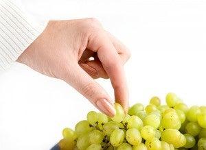 Mulher pegando uvas que são bons diuréticos naturais