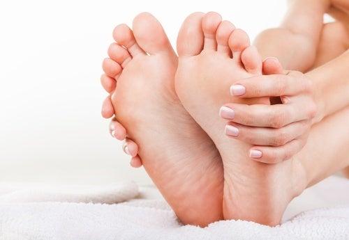 Mulher pegando nos pés para alongar o corpo