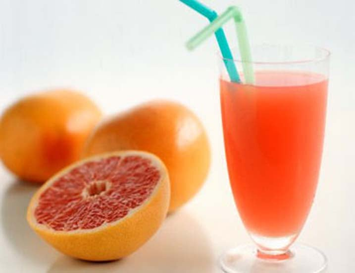 Glass of pink grapefruit juice beside fresh grapefruits