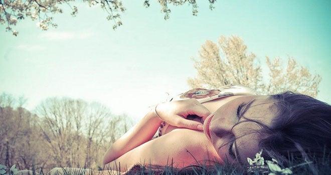 Mulher deitada em um parque pensando na influência de suas emoções em seus sonhos