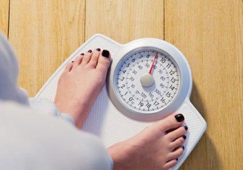 Mulher se pesando na balança com influência do vinagre de maçã