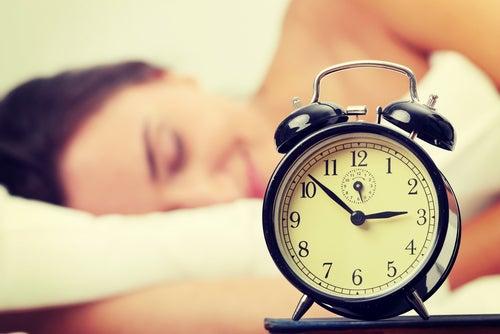 Mulher dormindo com o despertados por perto. Dormir ajuda a cuidar dos ossos.