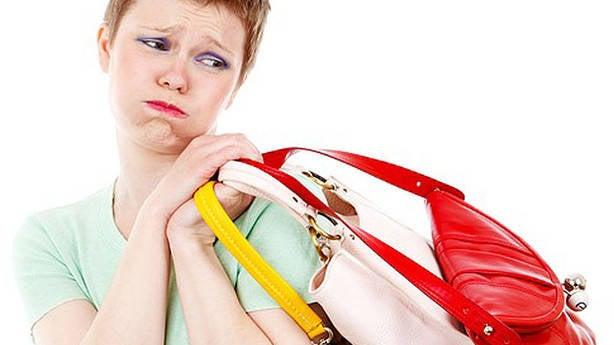 Mulher carregando bolsas pesadas. Isso pode prejudicar os ossos das mãos e dos braços.