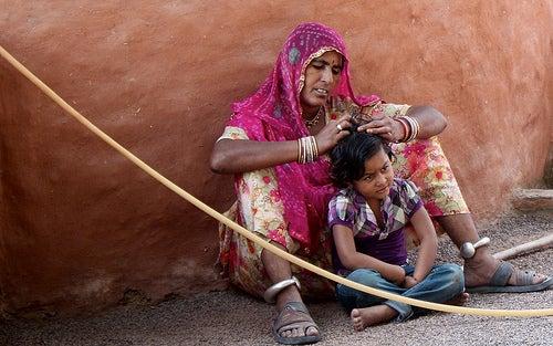 Mulher catando piolhos na cabeça de uma criança