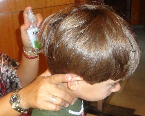 Mulher aplicando remédio de piolho no cabelo do filho