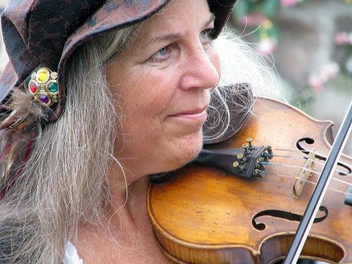 Mulher com fios brancos tocando violino
