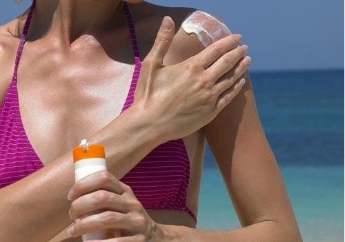 Mulher colocando protetor solar para evitar câncer de pele
