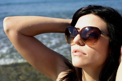 Mulher tomando sol com óculos