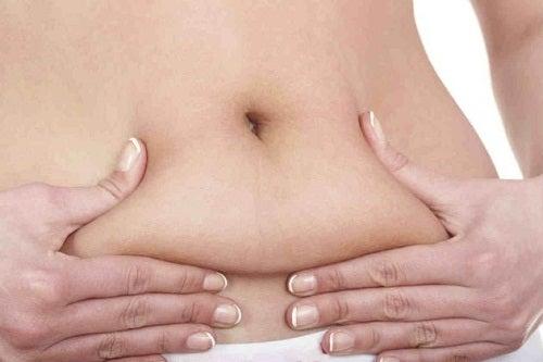 Mulher apertando gordura abdominal pensando em quantas calorias por dia ela pode perder