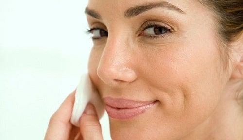 Mulher utilizando algodão com alho para cuidar da pele