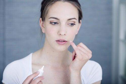 Mulher passando remédio em herpes labial