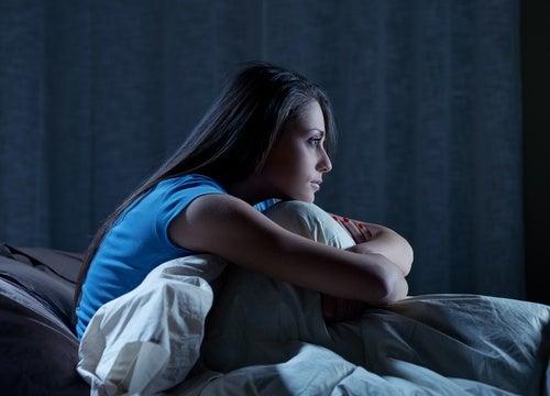 mulher com insônia pensando em como dormir