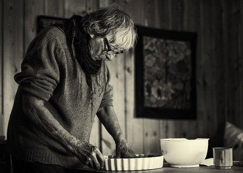 Mulher idosa fazendo comida cansada devido a Síndrome do cuidador