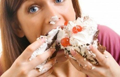 Mulher comendo bolo com gordura ou o açúcar