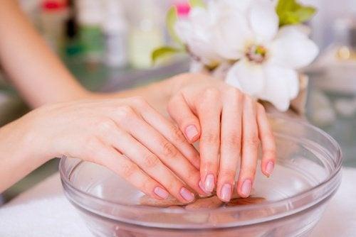 Mulher molhando as mãos antes de fazer a manicure