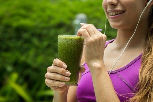 Mulher tomando vitamina verde para diminuir a hipertensão e limpar os rins
