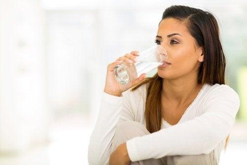 Mulher bebendo água para evitar infecção na bexiga
