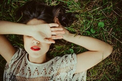 Mulher deitada na grama debatendo seus pensamentos
