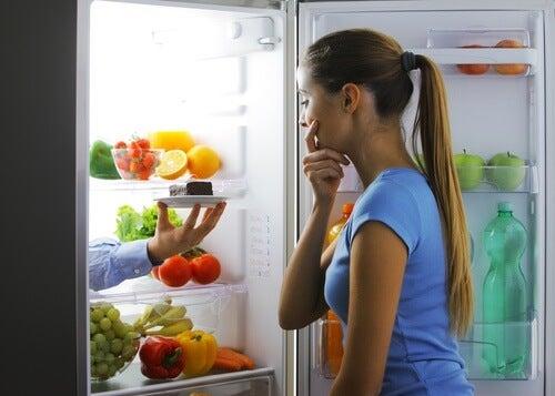 Mulher olhando para a geladeira pensando em quebrar suas dietas