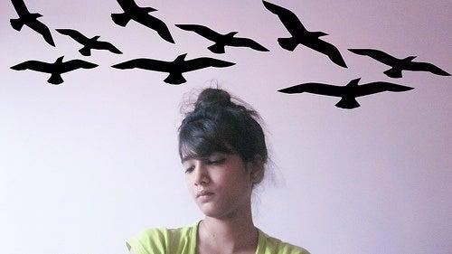 Mulher com ilustração de pássaros voando na cabeça por falta de cloreto de magnésio