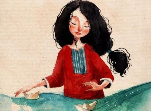 Mulher desfrutando da vida brincando com barquinho de papel