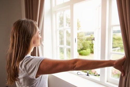 Mulher abrindo a janela para arejar o quarto