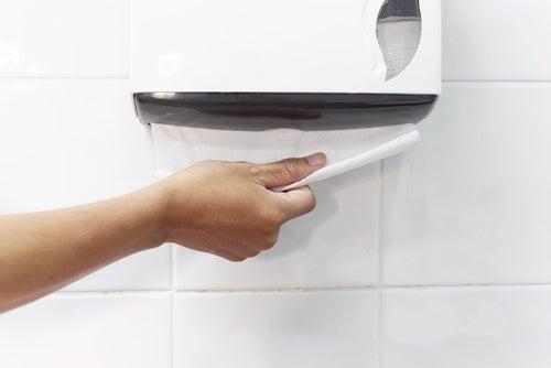 Mulher que usa banheiro público tirando papel