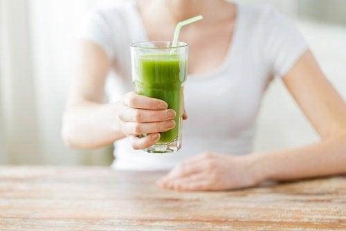 Mulher-segurando-copo-suco-verde