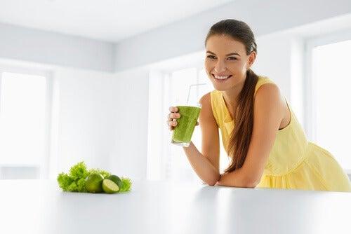 Mulher bebendo uma vitamina relaxante de abacaxi, menta, maçã e limão