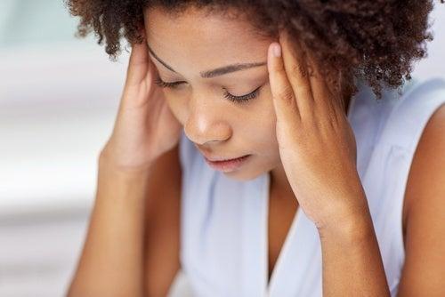 Mulher com dor de cabeça devido a doenças cardiacas