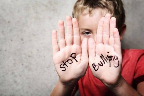 Menino-mostrando-mensagem-de-parar-com-o-bullying