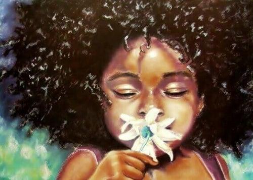 Menina fechando os olhos e cheirando uma flor