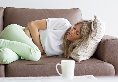 Mulher com dor de estômago por causa do supercrescimento bacteriano