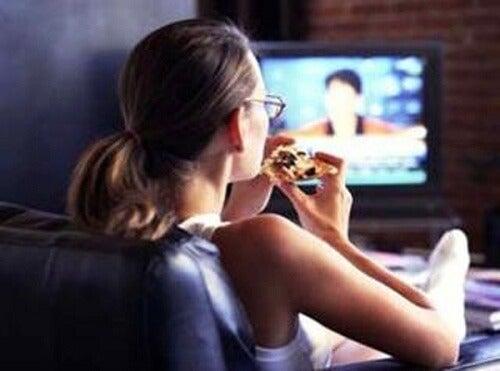 Mulher comendo na frente da televisão
