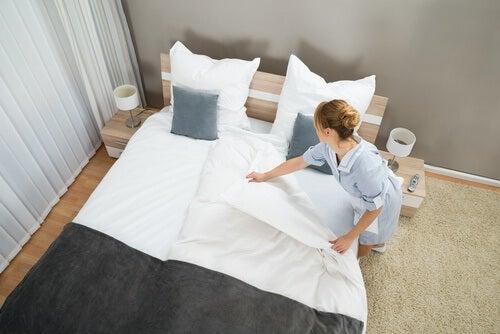 Mulher colocando lençóis lavados na cama
