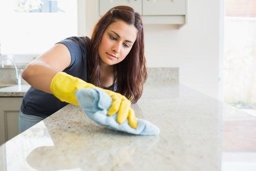 Mulher limpando a bancada com produtos naturais