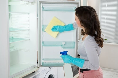 Mulher limpando a geladeira com produtos naturais