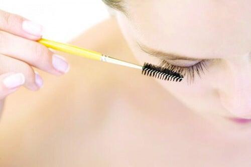 Mulher escovando os cílios com escovinha de rimel