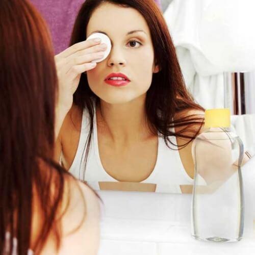 Mulher removendo maquiagem dos olhos com óleo para bebês