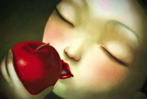 Menina mordendo uma maçã e dando valor ao seu sabor