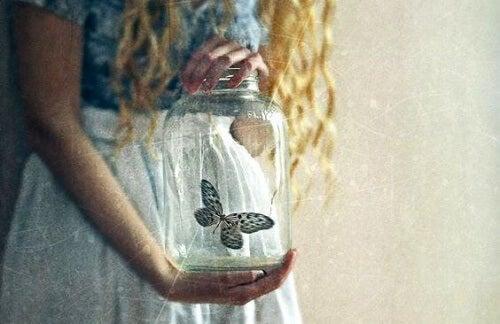 mulher-segurando-pote-de-vidro-com-borboleta-500x324