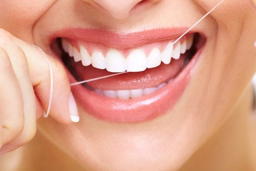 Mulher passando fio dental para combater o mau hálito