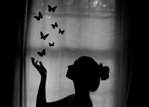 Mulher com borboletas deixando ir a falsidade