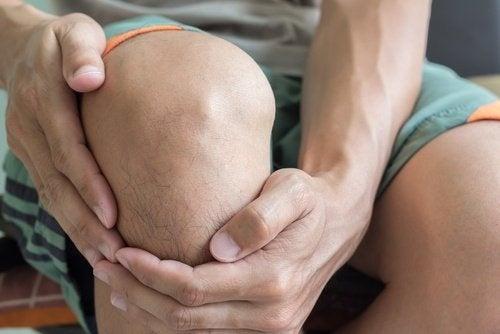 Homem com dores nos joelhos