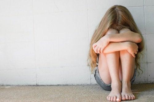 Menina triste pelo comportamento tóxico dos pais