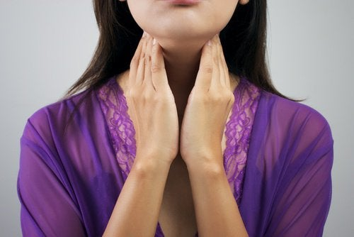 Mulher apalpando a tireoide