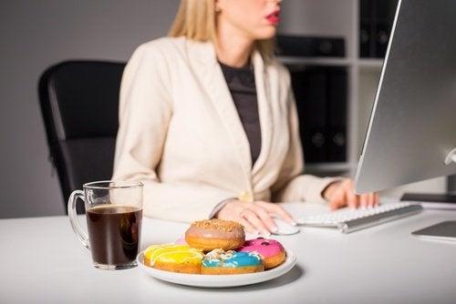 Mulher com enxaqueca por comer enquanto trabalha