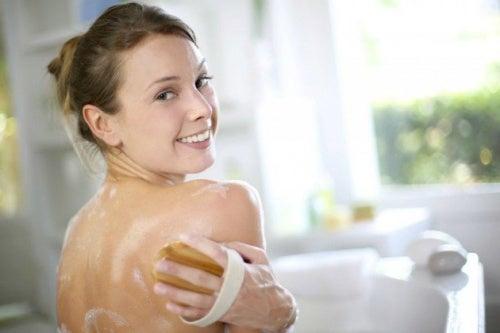 Mulher exfoliando as cosatas para evitar acne