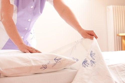Mulher arrumando a cama do quarto