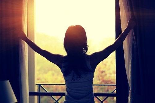 Mulher abrindo as janelas de seu quarto
